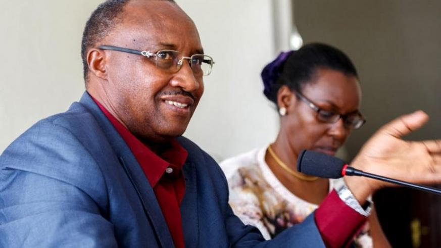 Protais Musoni, the chairperson of the Rwanda Chapter of the Pan-African Movement (L), speaks during the meeting with heads of political parties as his deputy, Henriette Umulisa, looks on.(Timothy Kisambira)