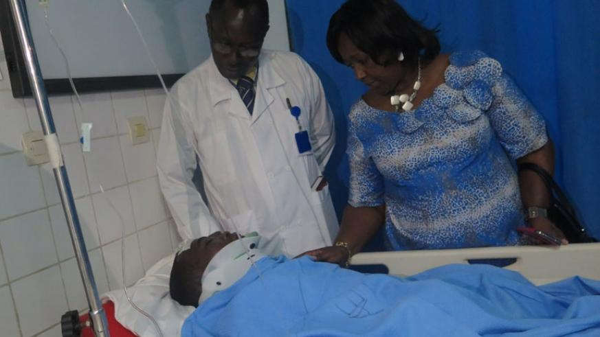 Minister of Health Dr. Agnes Binagwaho (R) and CHUK Direcfor, Dr. Theobald Hategekimana check on Etienne Nsanzimana who was injured in the accident yesterday (Jean Mugabo)