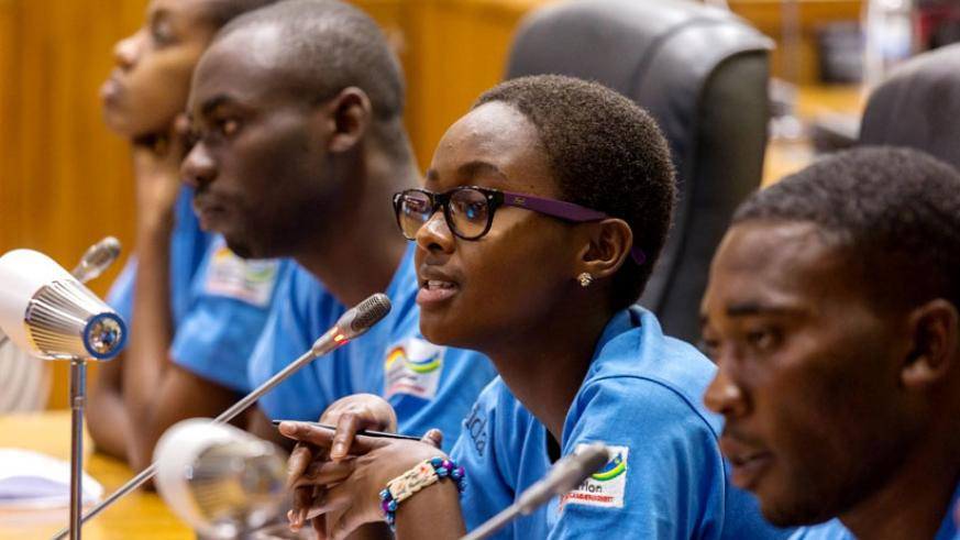 Assia Umuranga (C) from Groupe Scolaire Gatagara in Huye District speaks at Parliament as Monicah Kayezu (L), Jean Claude Urengejeho (2ndL)  and  Jean Claude Makuza (R) look on.  (All photos by Timothy Kisambira)