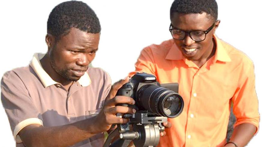 Yves Amuli (R) shows an unidentified man how to use a camera. (Courtesy photo)