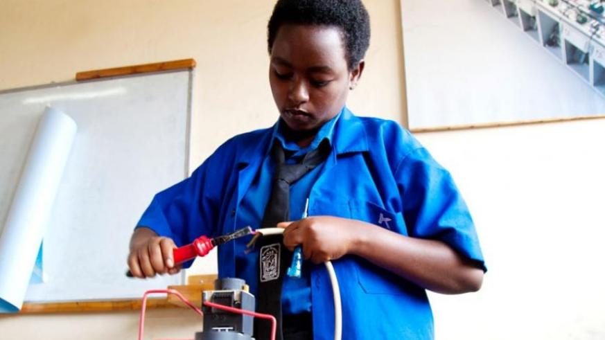 Charlene Byukusenge, a vocational student from Groupe Scolaire ADB Nyarutarama High School in Gasabo District, fixes her project of design and implementation of sound signaling system at SOS Hermann Gmeiner Technical High School in Kagugu, Gasabo. (Timothy Kisambira)
