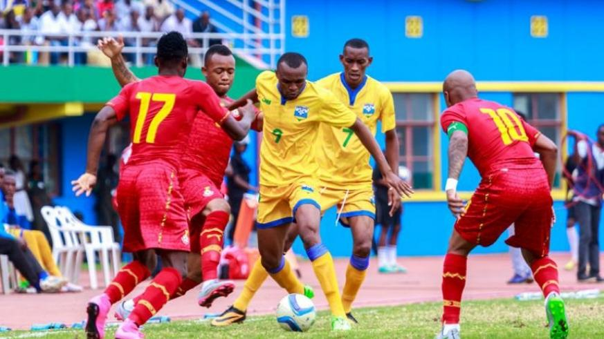 Rwanda's Jacques Tuyisenge (number 9) takes control of the ball against Ghana's Baba Rahman (L) and Dede Ayew (R) earlier this month in AFCON 2017 qualifier. (Timothy Kisambira)