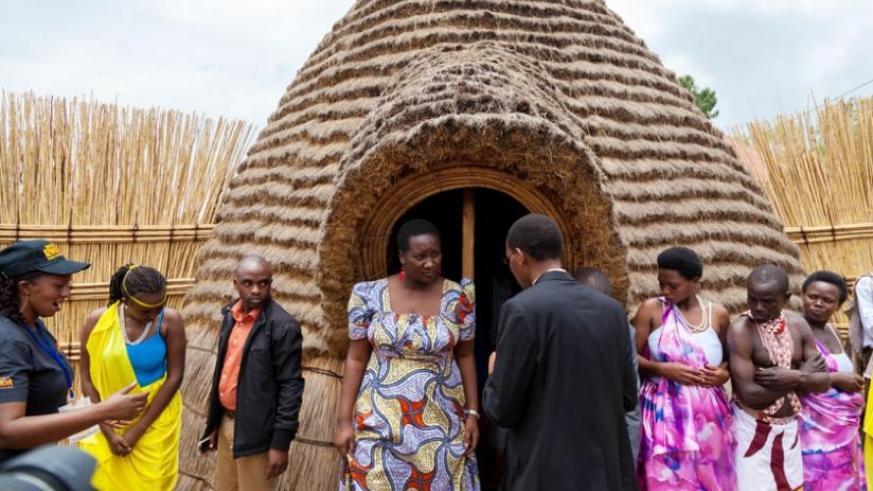 Sports and Culture minister Julienne Uwacu (L) is briefed by Philbert Musanganya, the head of Rulindo Cultural Centre, as she emerges from a tour of one of the traditional houses at the centre. (Timothy Kisambira)