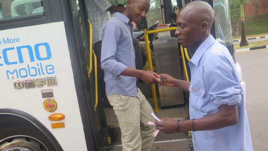 A KBS conductor gives a passenger a ticket at MINIJUST stage, Kimihurira. Passengers will soon start paying bus fares using swipe cards. (Jean Mugabo)