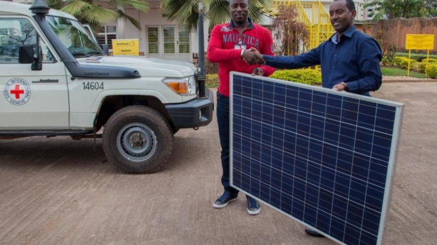 Rugero (R) hands over the solar panel to ICRC's Dukuze on Tuesday. (Faustin Niyigena)