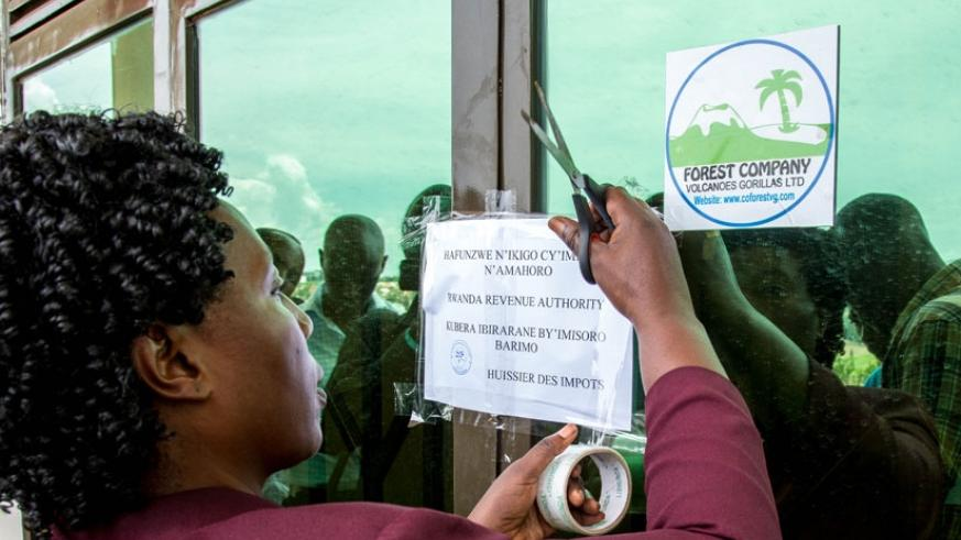 An official puts a notice of closure at the entrance of Forest Company yesterday. (Doreen Umutesi)
