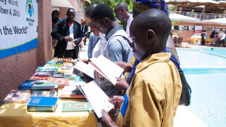 People read books at an exhibition stall on Tuesday. (Teddy Kamanzi)