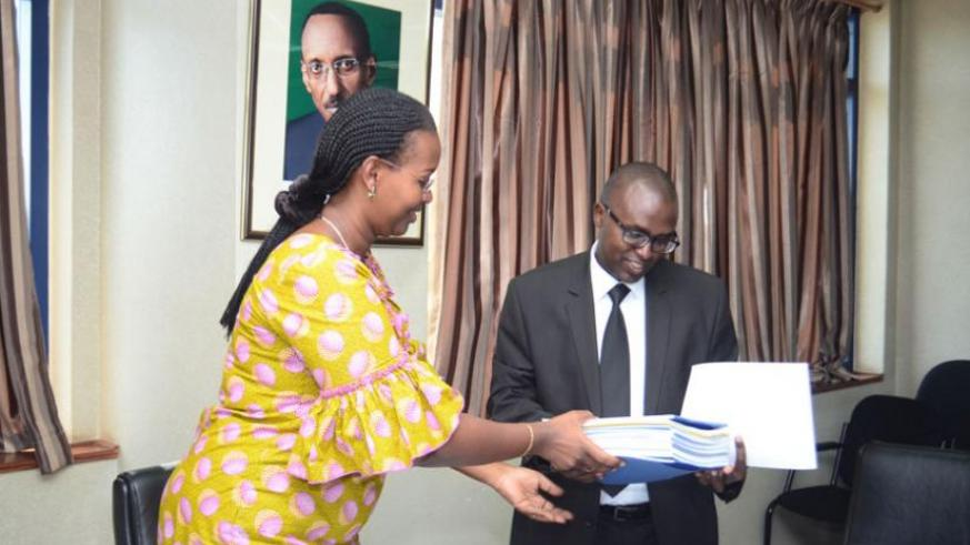 (L_R): Dr Solange Hakiba, the permanent secretary at the ministry of health handing over Mutuelle documents to Jonathan Gatera, the RSSB director general. (Theogene Nsengimana)
