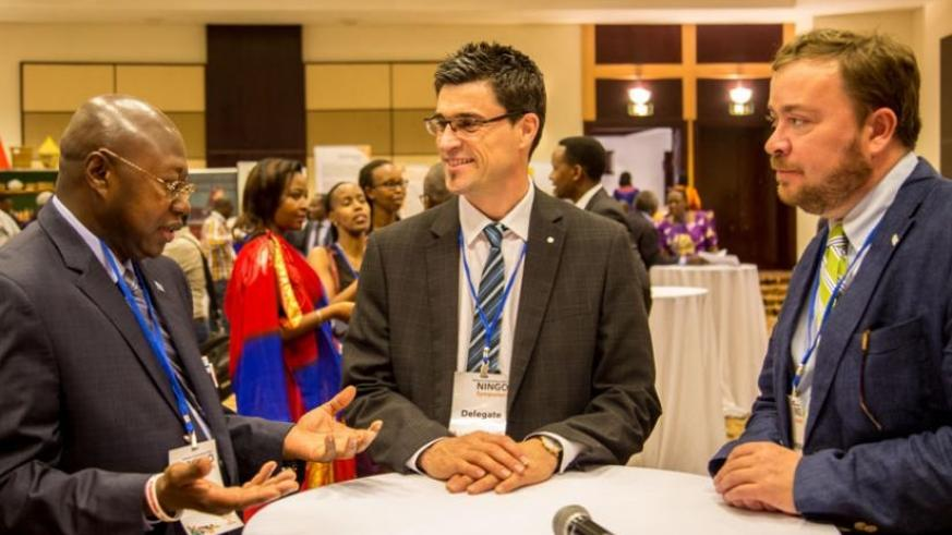Manneh (L), Auger (C) and John Ames, the chief of party of Global Communities, chat during a break during the NINGO meeting in Kigali yesterday. (Doreen Umutesi)