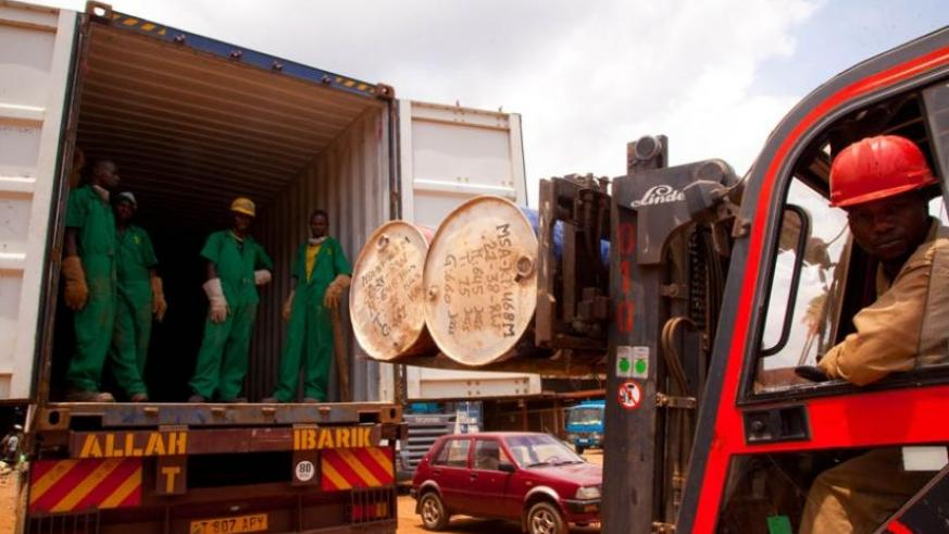 Workers at Mineral Supply Africa Company load containers of minerals on to trucks. (Timothy Kisambira)
