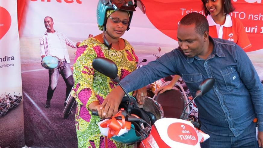 Urayeneza (left) is guided by Airtel staff to start the motorcycle. (Courtesy photo)