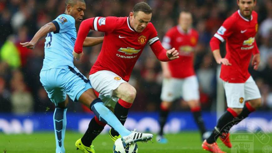 Man United captain Wayne Rooney tries to charge past Man City's Fernandinho last season. (Net photo)