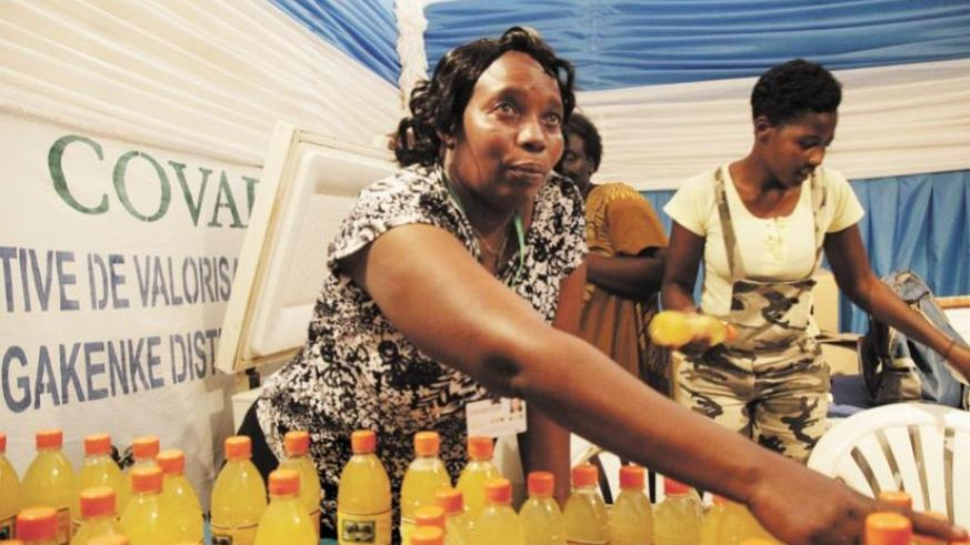 A Gakenke District juice producer talks to clients about her products at an exhibition in this 2013 photo. SMEs need to have solid HR strategies, too. (File)