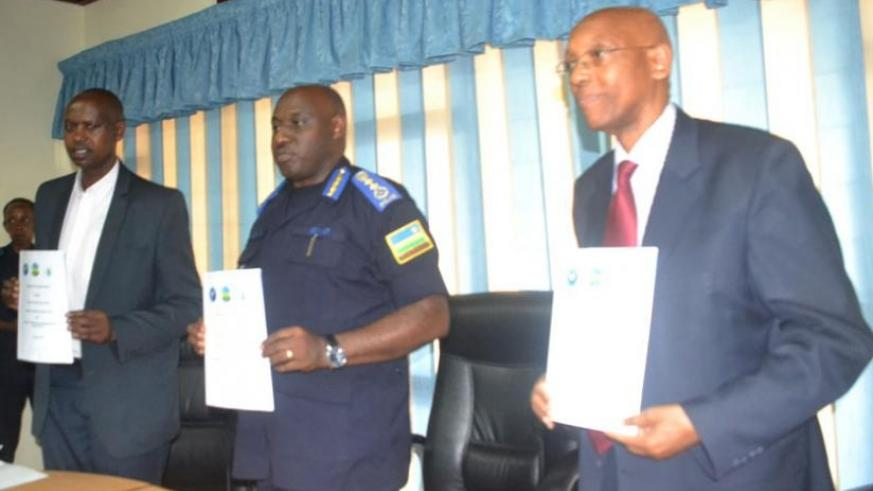 L-R: Augustin Katabarwa, the chairman of NCCR, IGP Emmanuel K. Gasana and Damien Mugabo, the director-general of RCA, display copies of the MoU they signed yesterday. (Courtesy)