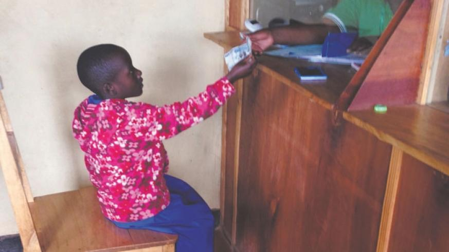A cashier at a microfinance attends to a young saver. Mobilising savings is key for a country's growth.  (P. Tumwebaze)