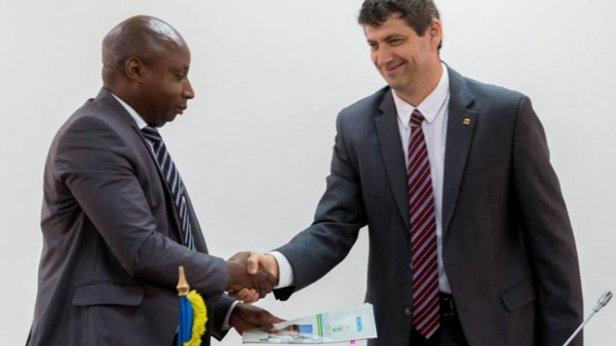 Mugiraneza (L) exchanges documents with Weiss in Kigali, yesterday, after the two signed agreements that will see Israel Electric Corporation help REG in its efforts to generate 563 megawatts capacity by 2018 and connect 70 per cent of the country's households to electricity. (Timothy Kisambira)