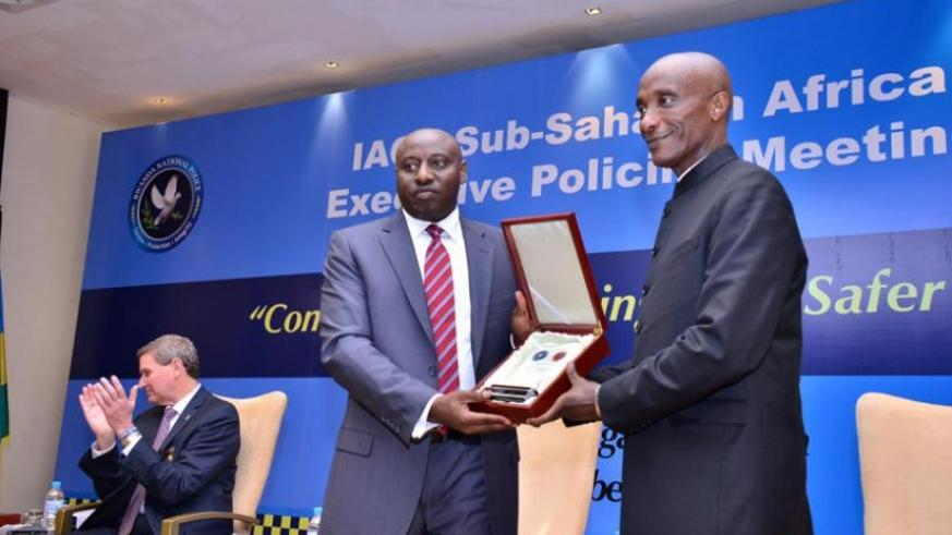 Inspector General of Police Emmanuel K. Gasana presents a souvenir to his Ugandan counterpart, Gen. Kale Kayihura, to whom he handed over the International Association of Chiefs of Police regional chair. (Courtesy)