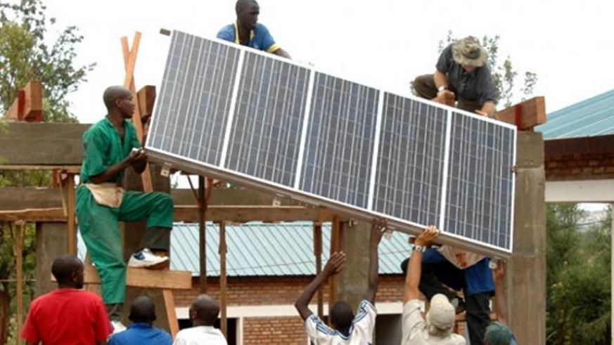 Workers instal a solar panel on a building in Kigali. (File)