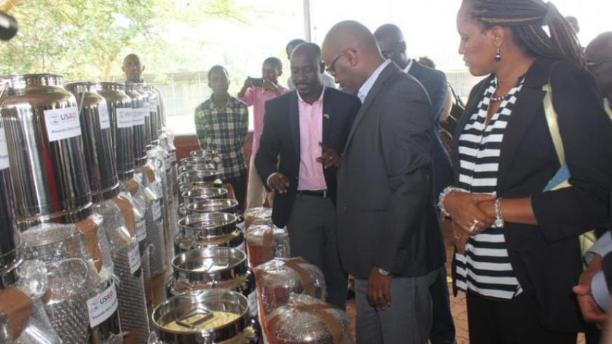 Karamuzi(L) and other officials inspect the dairy equipment donated by USAID. (John Mbaraga)