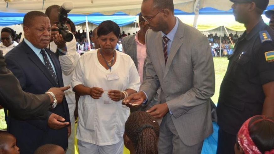 Bosenibamwe (left), a nurse (middle) and Kamanzi (right) give medicine to children at the launch of the week-long national campaign. (Jean Fidele  Ndungutse)