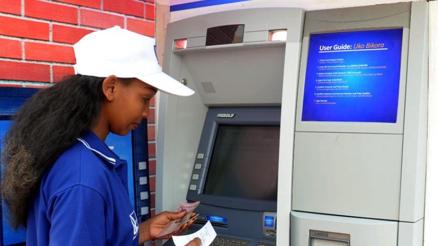 A Bank of Kigali client withdraws money at an ATM that accepts Visa, UnionPay, Diners Club International and RSwitch cards. Most businesses in Kigali now have POS to facilitate a cashless economy. ( File)