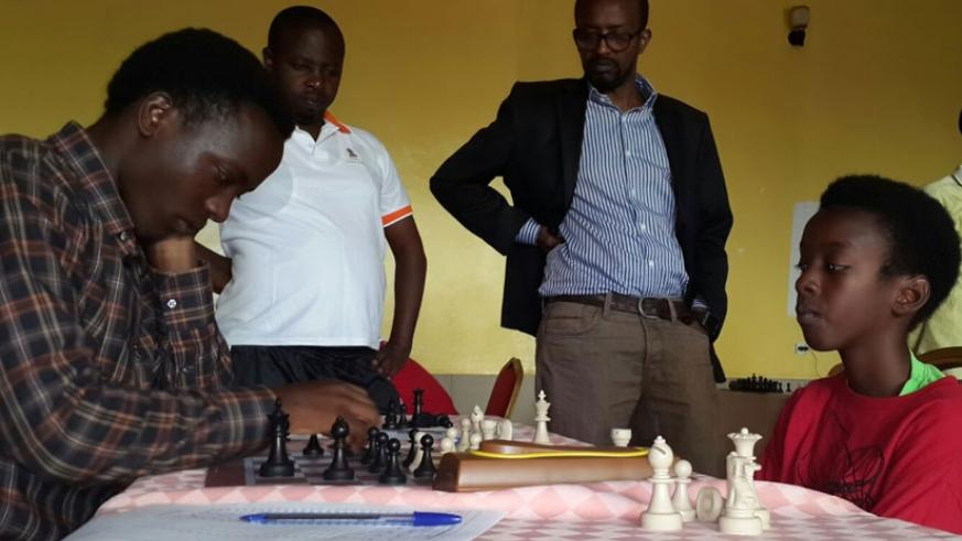 Ian Murara, right, gives University of Kigali (UK) student Elysee Tuyizere, 22, a hard time as his father, coach and teammate, Maxance Murara (in black coat), watches. ( J. Karuhanga)