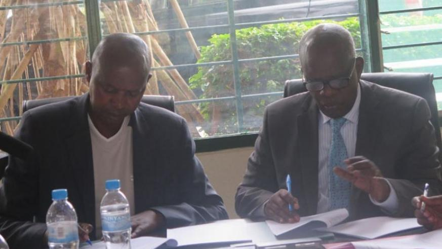 Katabarwa (L) and Nzagahimana sign  the  Memorandum of Understanding at Rwanda Institute of Cooperatives, Entrepreneurship and Microfinance Office in Kabusunzu on Friday. (Frederic Byumvuhore)