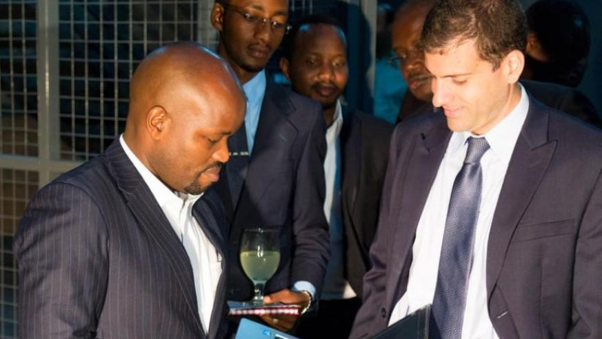 Jean Philbert Nsengimana, the Minister for Youth and ICT(L) and Juan Ponelli, the Positivo BGH Africa president (R), look at a laptop made in Rwanda at the event to launch a partnership to distribute locally made electronics on Friday. (Timothy Kisambira)