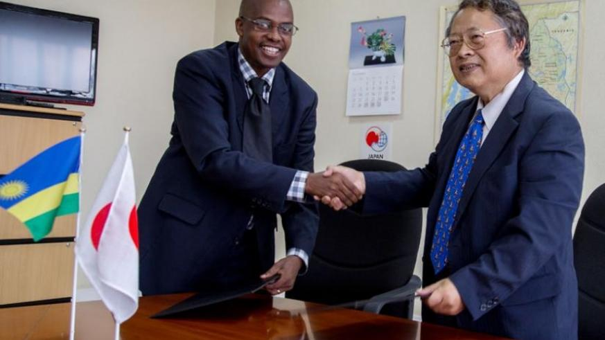 Munyurangabo (L)  and Sakamoto exchange a contract after the signing at the Embassy of Japan in Kigali yesterday. (Doreen Umutesi)