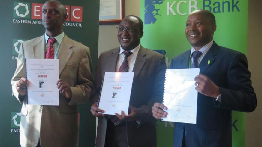 Rwibasira, Masila and Toroitich display signed documents. The partnership seeks to boost agro-funding and grain production. (Shamim Nirere)