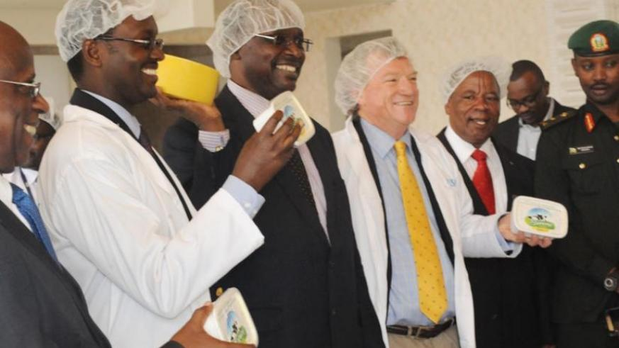 Minister Kanimba (2nd L) poses for photo with other officials showing cheese made from Burera dairy on Wednesday. (Michel Nkurunziza)
