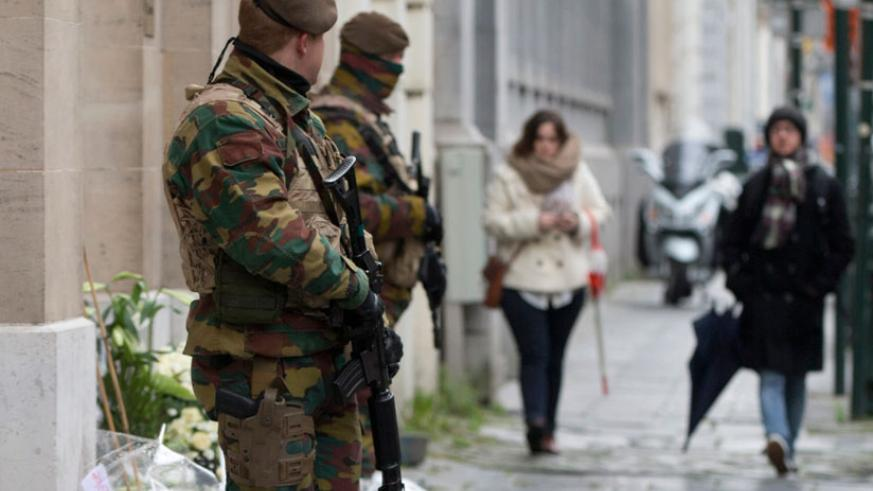 Belgian Army soldiers patrol next to flowers left in remembrance of terror attack victims in Brussels recently. (Internet photo)