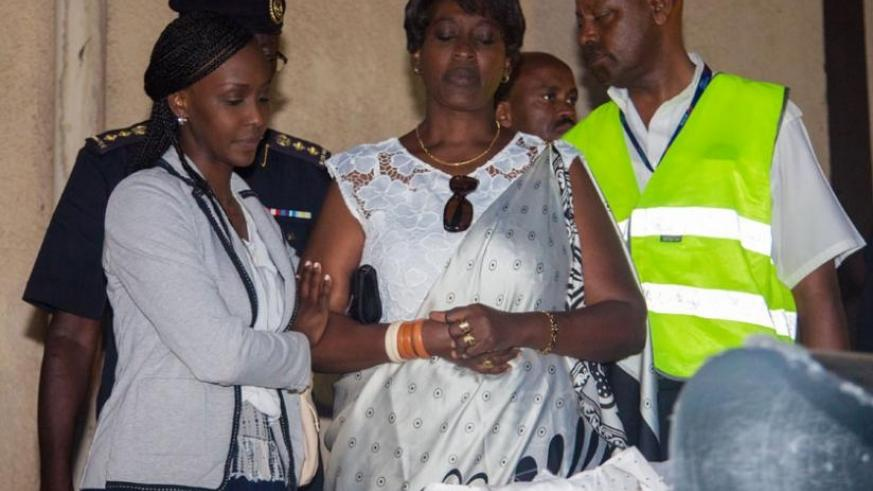 Bihozagara's widow, Jeanne Bihozagara and their daughter Bonita Isaro look at the casket containing the remains of the former Cabinet minister and diplomat, upon its arrival at  Ki....