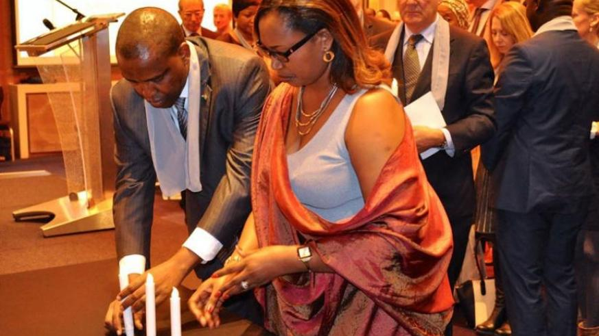 Amb. Karabaranga and his wife light a candle during the commemoration event in Netherlands. (Courtesy)