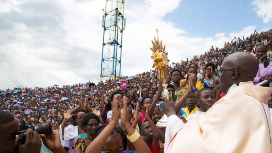 Father Ubald Rugirangoga raises a holy cross to pray for Christians who turned up at Amahoro Stadium for the healing mass yesterday. (Timothy Kisambira)