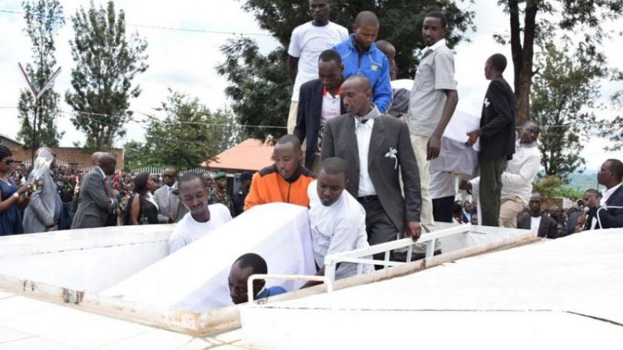 Bodies being lowered into the grave at Kiziguro memorial site on Monday. (Kelly Rwamapera)