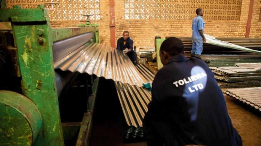 Workers of Tolirwa Industries pull ready-to-be-sold iron sheets from a machine. (File)