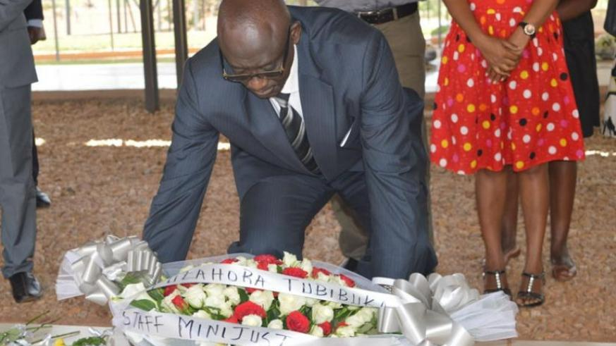 Minister Busingye lays a wreath on a grave at Nyanza-Kicukiro Genocide memorial on Monday. (J. Mbaraga)
