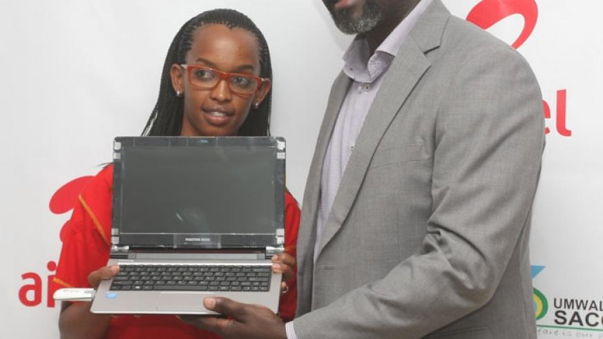 Onzoma (right) hands over a Positivo laptop to one of the Airtel agents that will train teachers in computer basic skills under the initiative. (Peterson Tumwebaze)