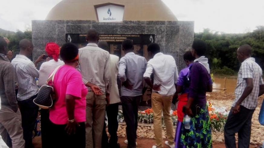 Mourners look at the names of the 755 victims of the 1994 Genocide against the Tutsi on a monument erected on the banks of Nyabarongo River on Saturday. (Emmanuel Ntirenganya)