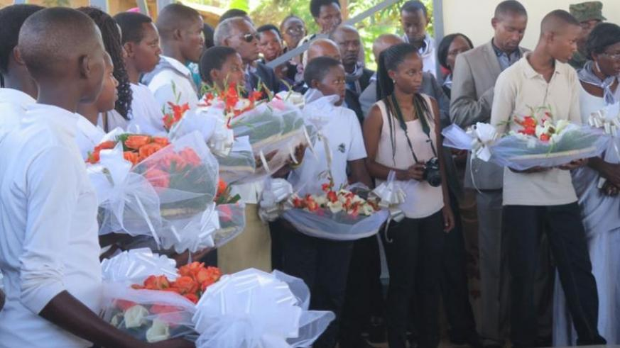 Grandchildren of victims of the Genocide queue to lay wreaths on a tomb. (Stephen Rwembeho)
