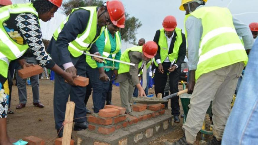 Governor Mukandasira (L) and Minister Kanimba (2nd left) lay the foundation of a new market to be constructed in Karongi. (S. Muvunyi)