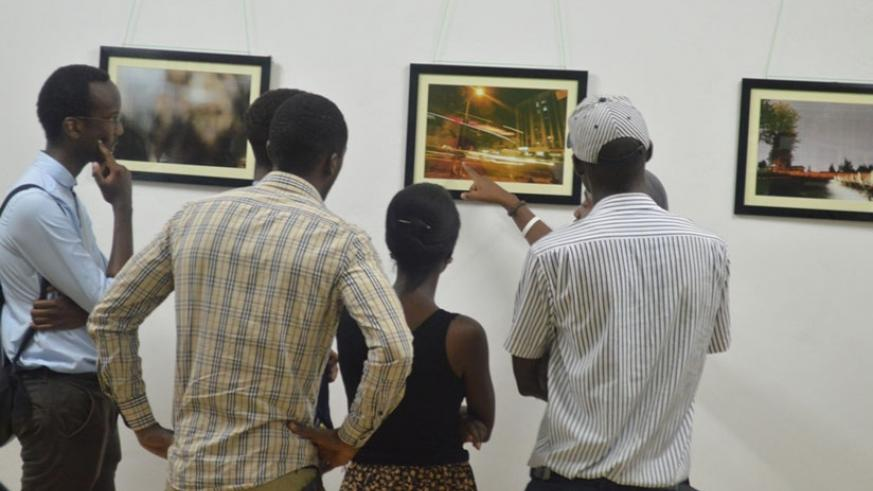 A photographer explains to guests about his work on display. (Julius Bizimungu)