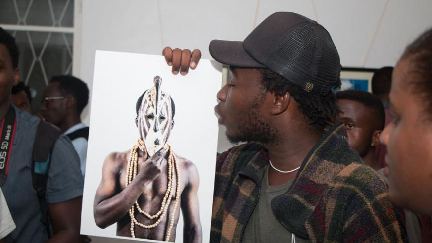 Jacques Nkinzingabo shows off one of his photos. (Moses Opobo)