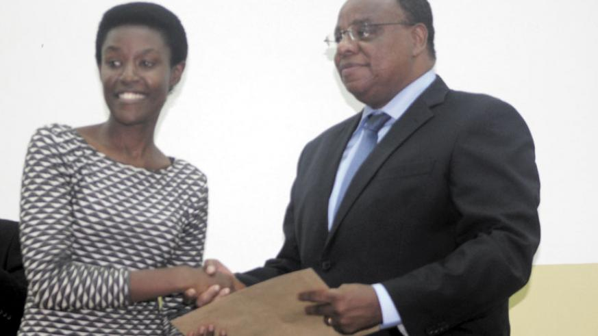The Kenya High Commissioner to Rwanda, H.E. John Mwangemi (R) handing over a CPA certificate to Jeanne Abayo, one of the graduates, at UR-CBE in Kigali on Thursday. (Courtesy)