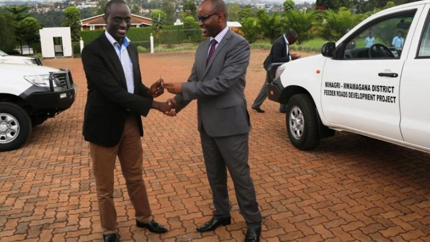 Musabyimana (right) hands over one of the car keys to  Kakooza, the Rwamagana District executive secretary at the agriculture ministry head offices. (Peterson Tumwebaze)