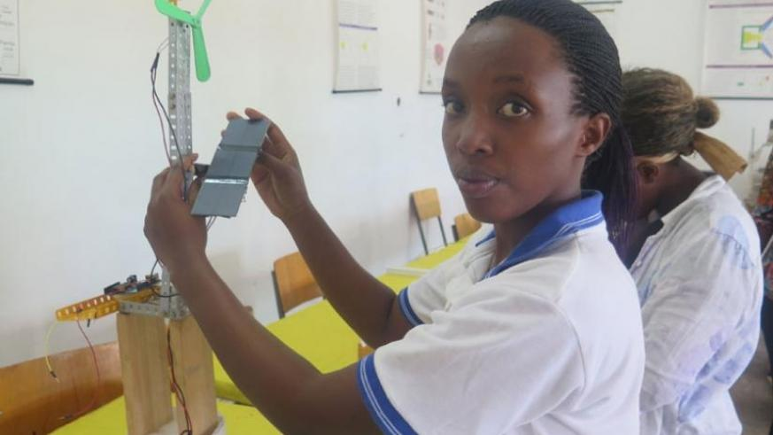 A student experimenting with a  solar and wind hybrid green tower as part of her research project.  (Solomon Asaba)