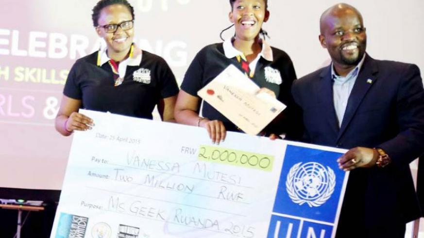 The Minister for Youth and ICT, Philbert Nsengimana hands over a dummy cheque to a past Ms. Geek winner. (Net photo)