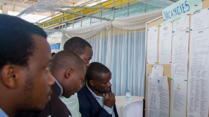 Jobseekers look for job opportunities on a notice board displayed at the third Kigali Employment Fair at Petit Stade in Remera, Kigali yesterday. (Timothy Kisambira)