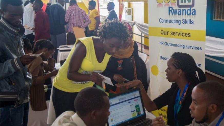 A staffer from Jobs in Rwanda organisation interacts with  jobseekers at Petit Stade in Remera, Kigali yesterday. (Timothy Kisambira)
